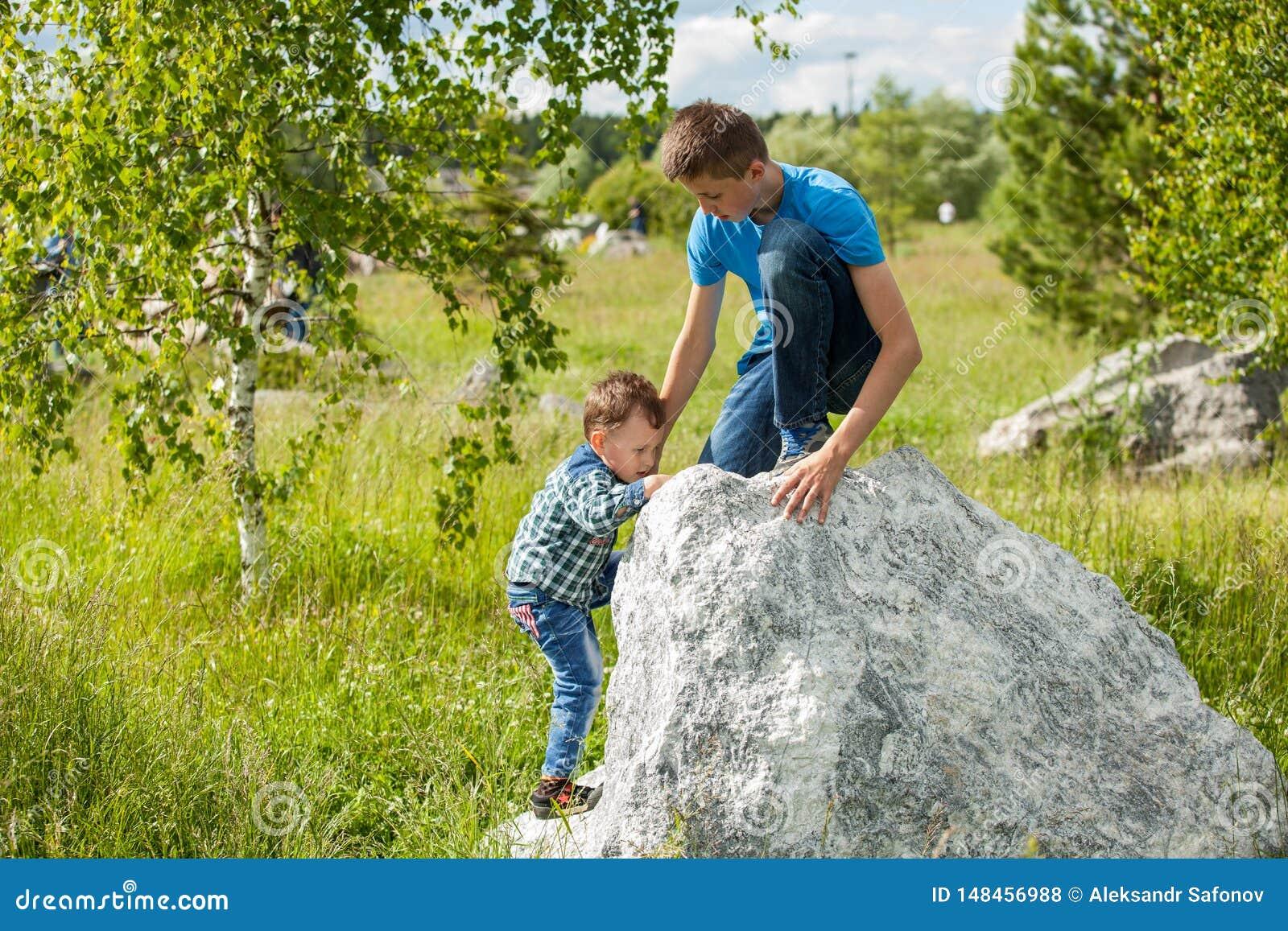 De kinderen helpen elkaar om de rots te beklimmen