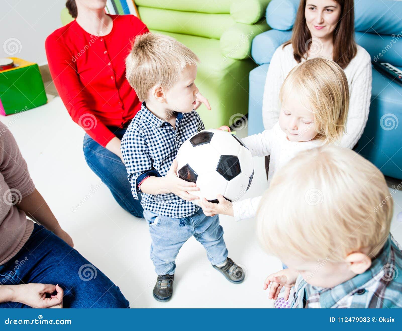 De kinderen rekken zich aan de bal uit
