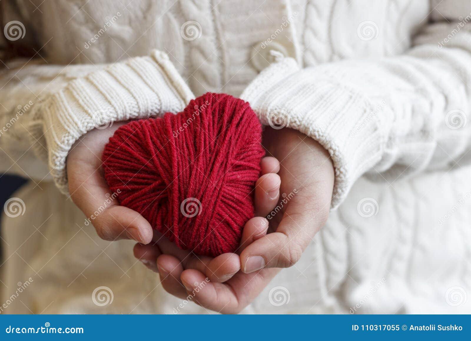 De kinderen` s handen houden een hart van rode draad voor het breien