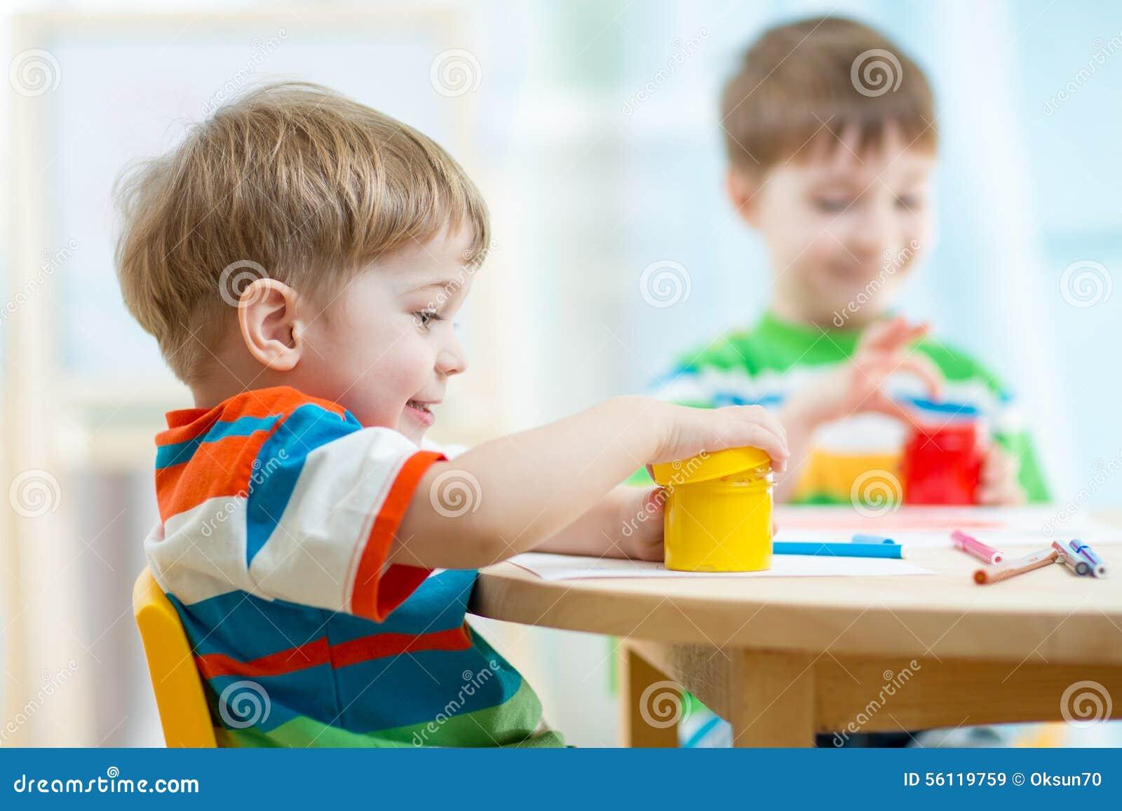 De kinderen spelen en schilderen thuis of kleuterschool of playschool stock foto afbeelding - Schilderen kind jongen ...