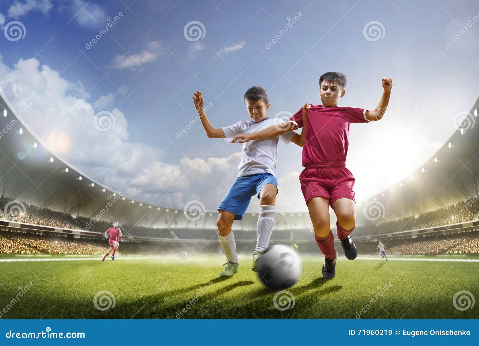 De kinderen spelen voetbal op grote arena