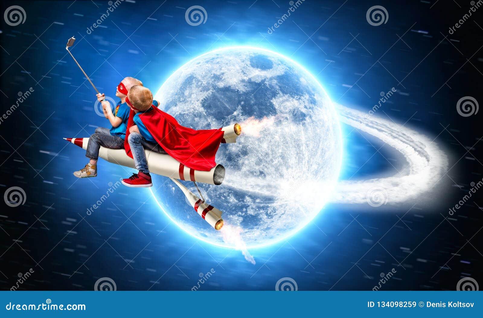 De kinderen in superherokostuums vliegen in ruimte op een raket en schieten een selfie op een mobiele telefoon