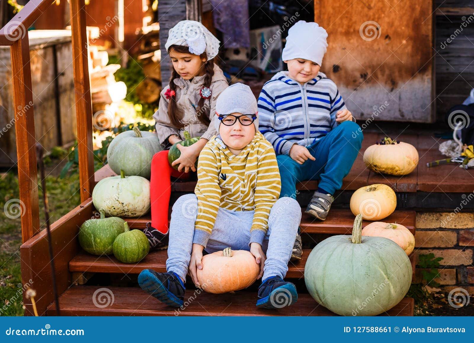 De kinderen zitten op de portiek met pompoenen