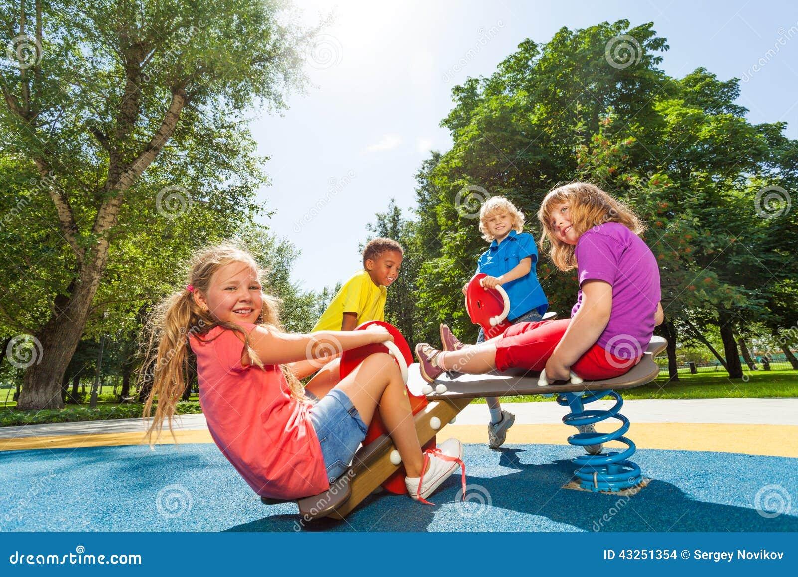 De kinderen zitten op speelplaatscarrousel met de lentes