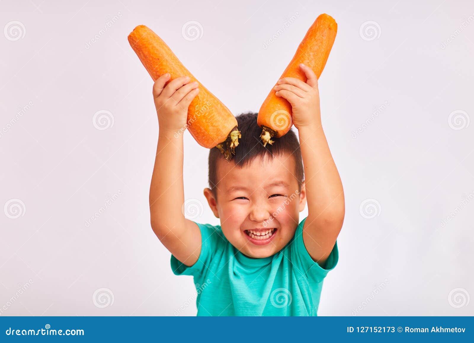De kindjongen in turkoois overhemd, houdt reusachtige wortelen afschilderend hoornen - vruchten en gezond voedsel