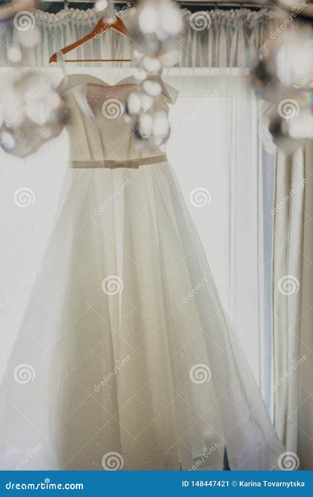 De kleding van het huwelijk Witte huwelijkskleding met een volledige rok op een hanger in de ruimte van de bruid met witte gordij