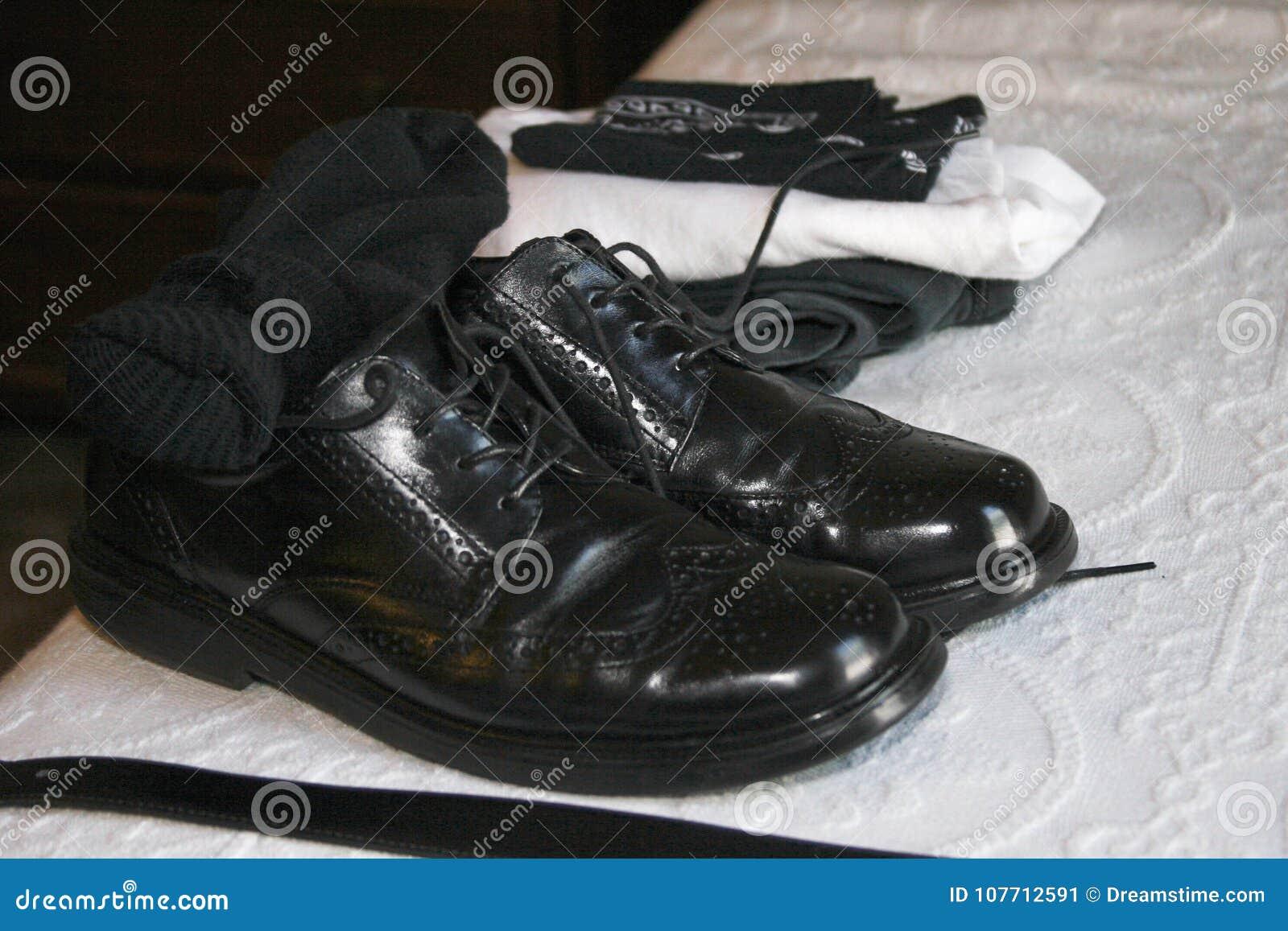 De kledingsschoenen van zwarte leer wingtip mensen met zwarte sokken en riem
