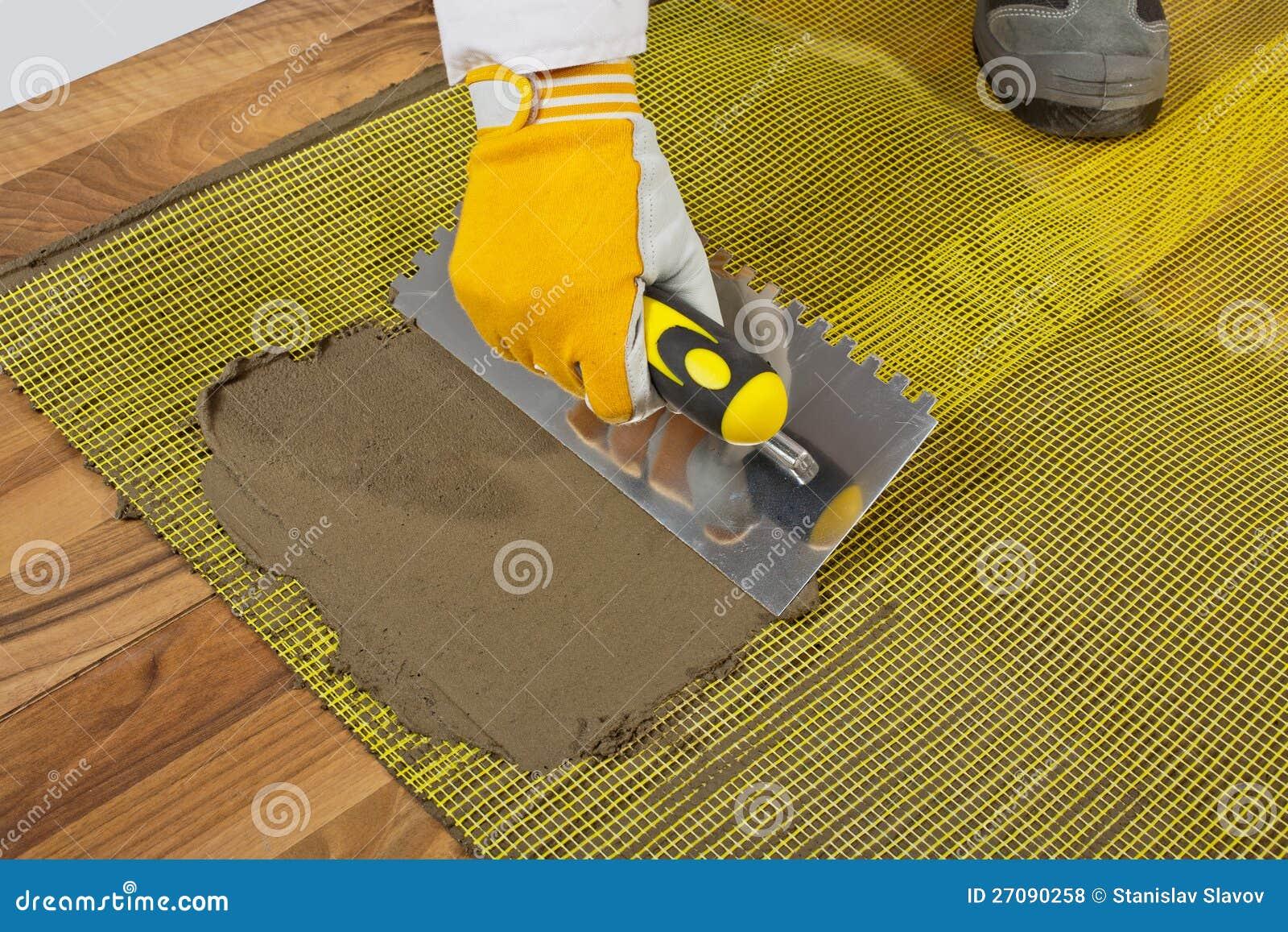 Houten Vloer Tegels : De kleefstof van de tegel op houten vloer stock foto afbeelding
