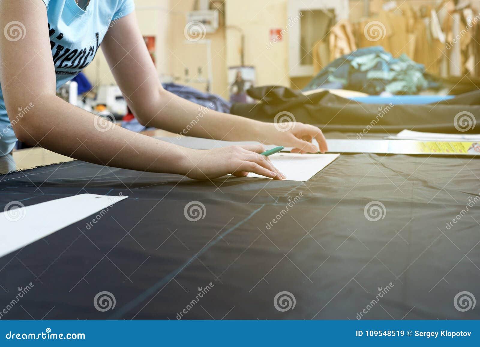 De kleermaker die met een scherp materiaal in een workshop bij a werken garmen