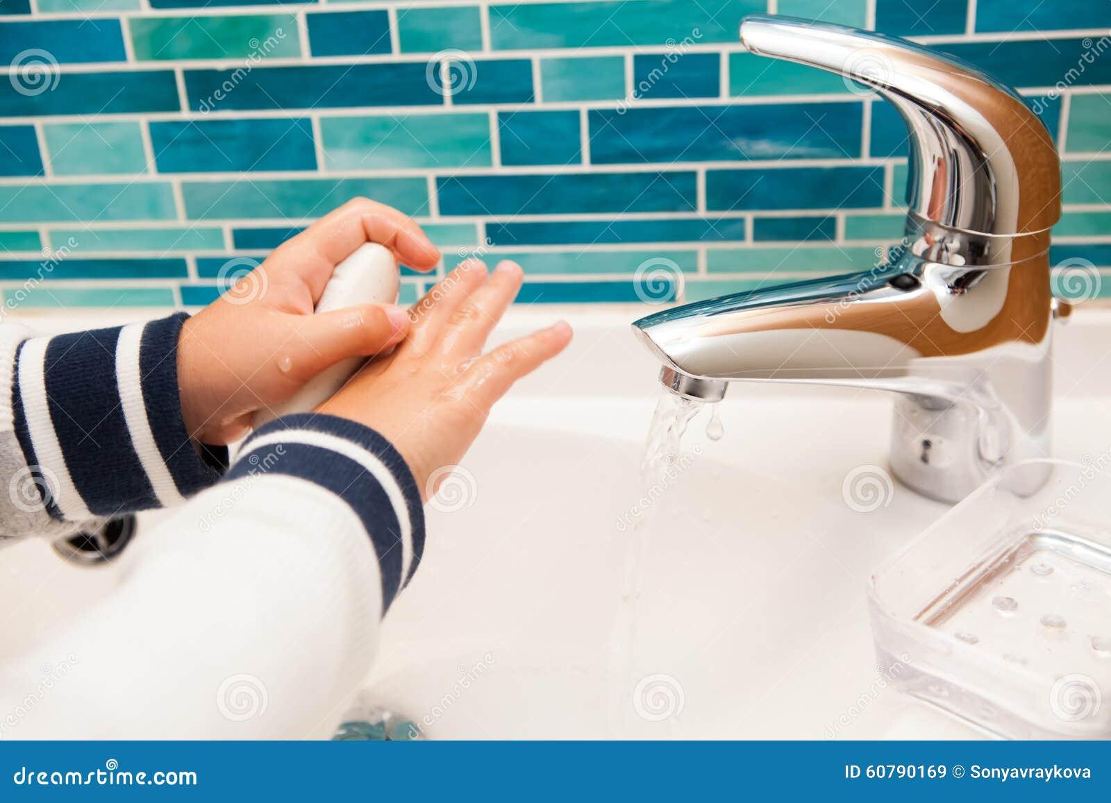 De kleine handen van de jongenswas
