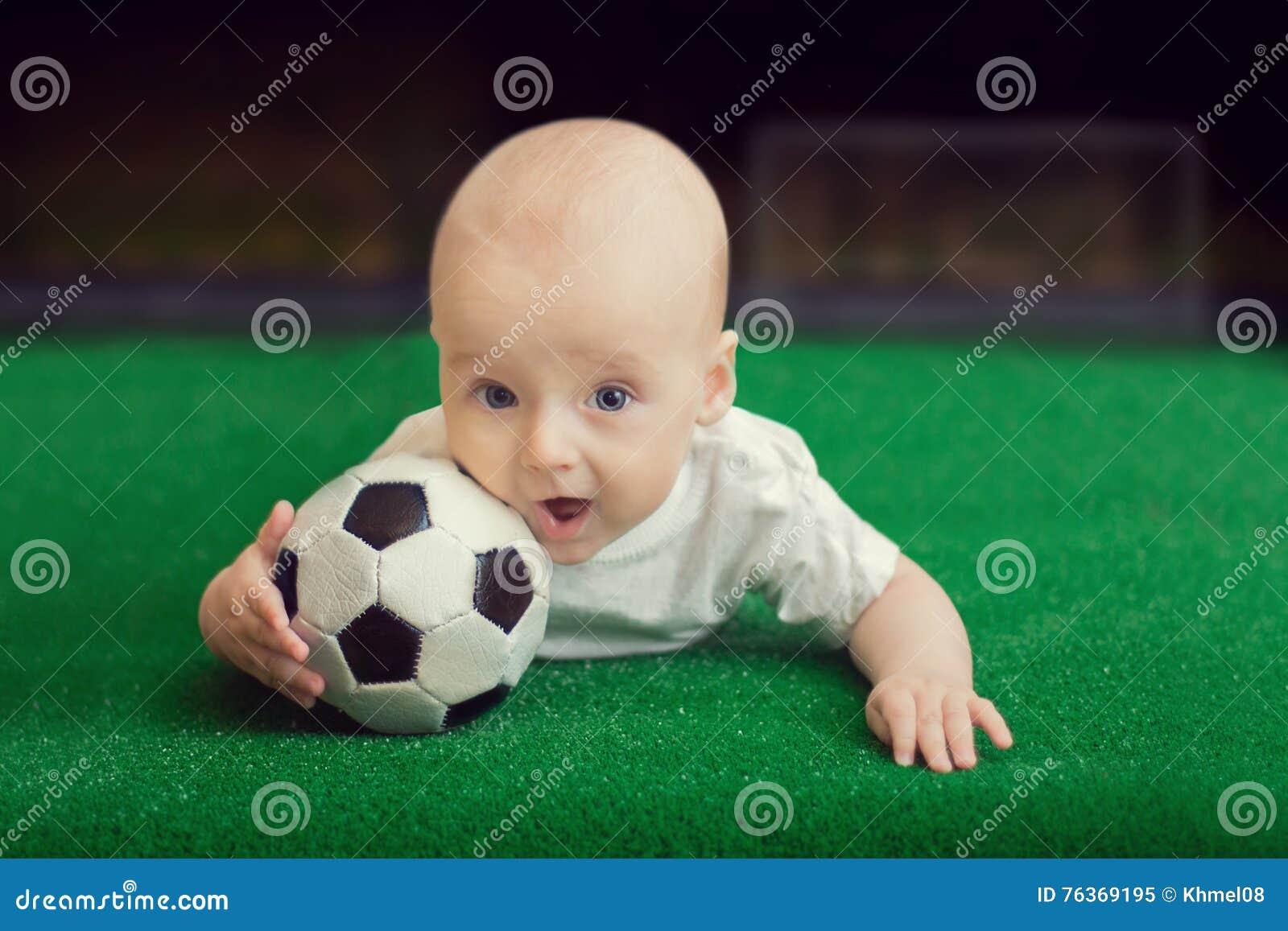 De Kleine jongen die op het gras met de bal liggen