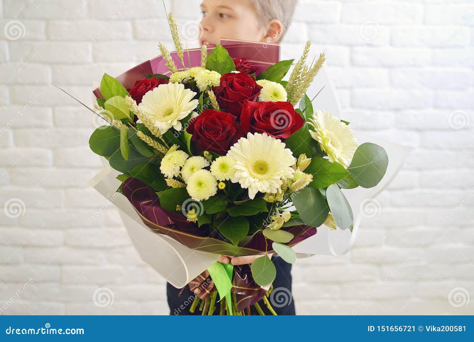 De kleine jongen met een groot boeket van bloemen