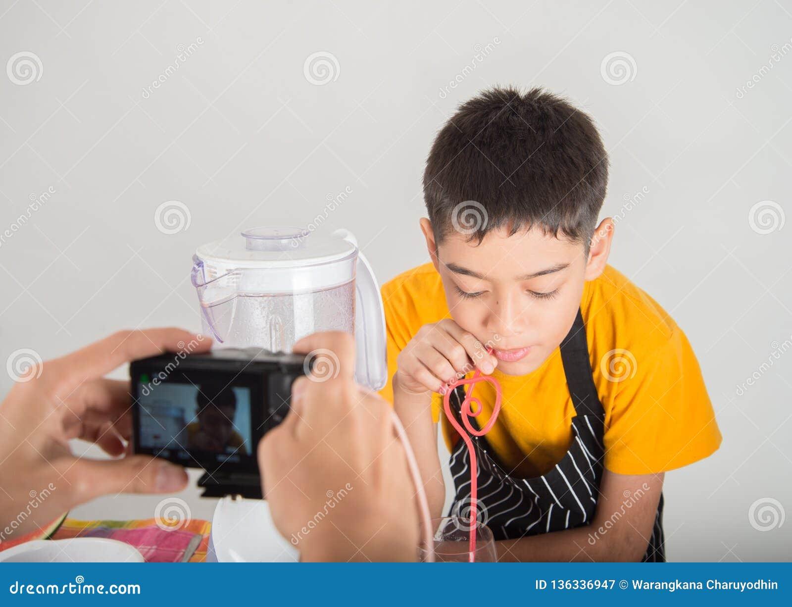 De kleine jongens mengen het sap van watermelone door mixerhuis te gebruiken