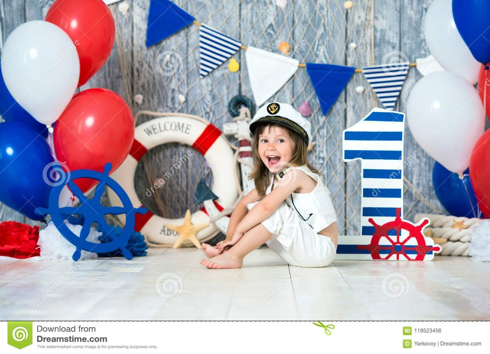 De kleine kapitein zit op de vloer in een mariene stijl Wij merken het eerste jaar