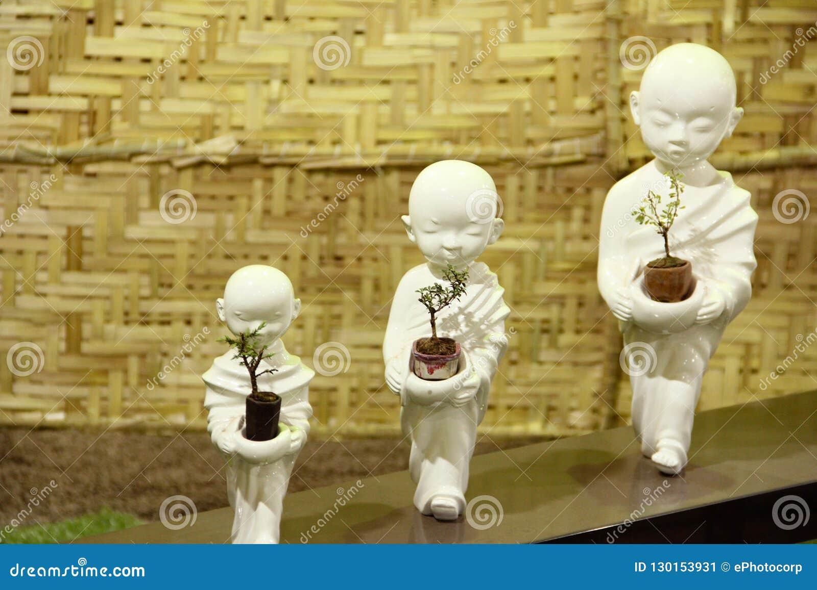 De kleine standbeelden die van Boedha Bonsaibomen, de tentoonstelling van de Bonsaiboom in Pune houden