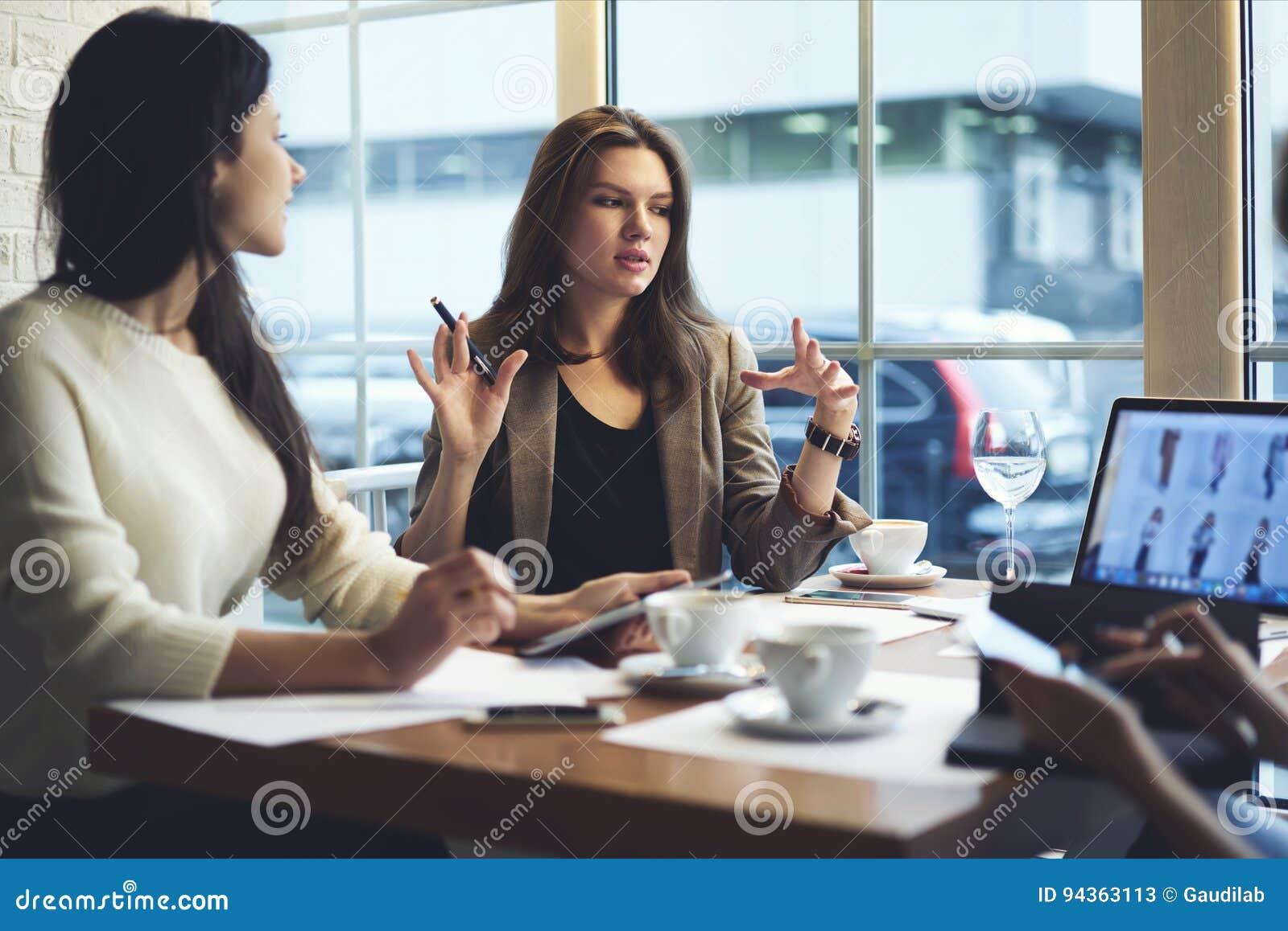 De kleren die van meisjesontwerpers aan online Webopslag samenwerken terwijl het hebben van vergadering met collega s in koffie