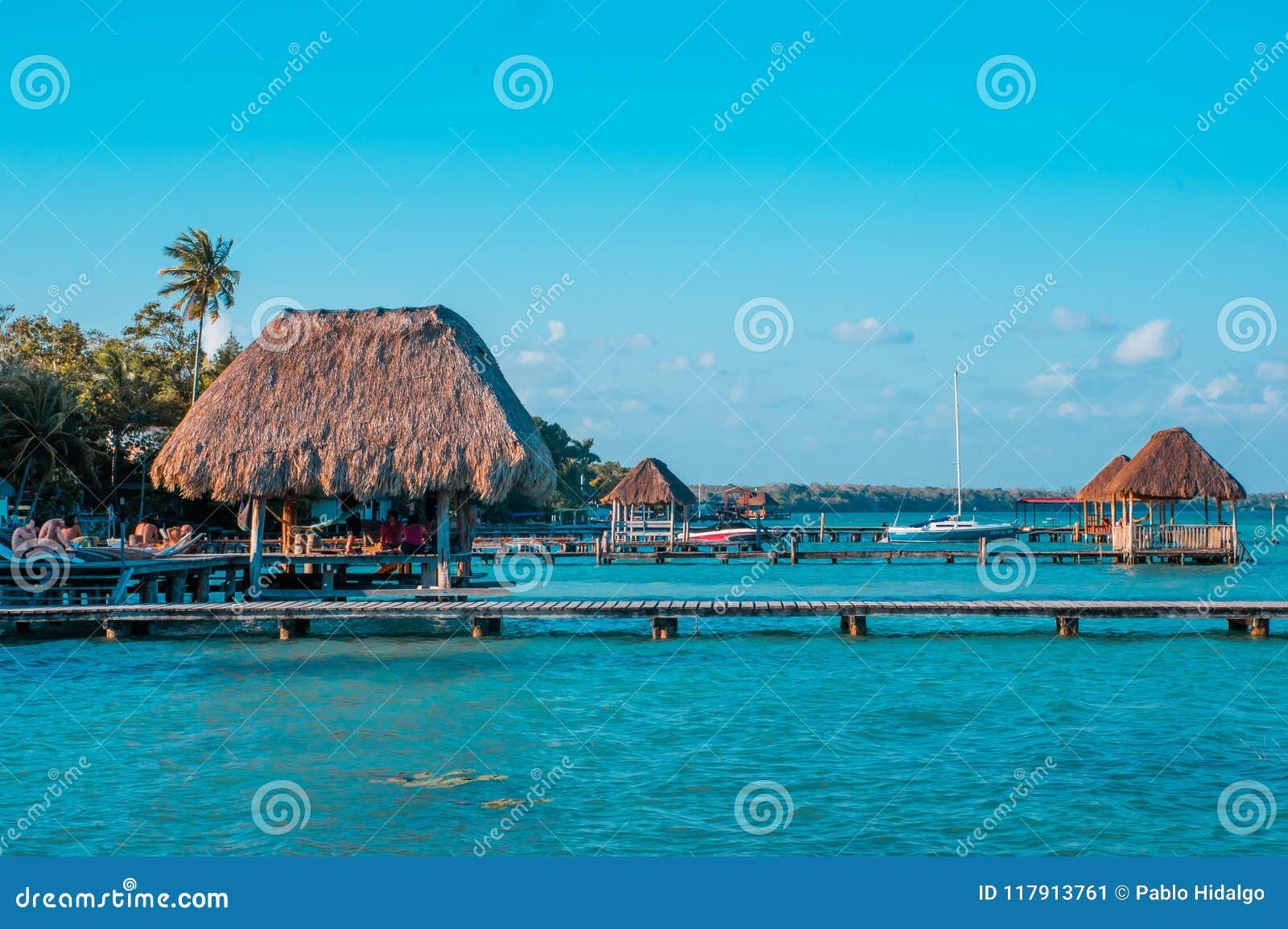 De kleur sorteerde beeld van een pijler met wolken en blauw water in Laguna Bacalar, Chetumal, Quintana Roo, Mexico