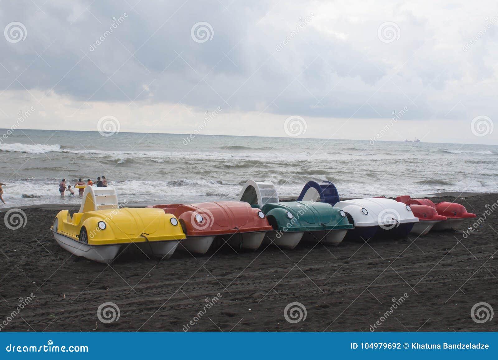 De kleurrijke boten van de pedalopeddel op het strand, bewolking, wolken, golven
