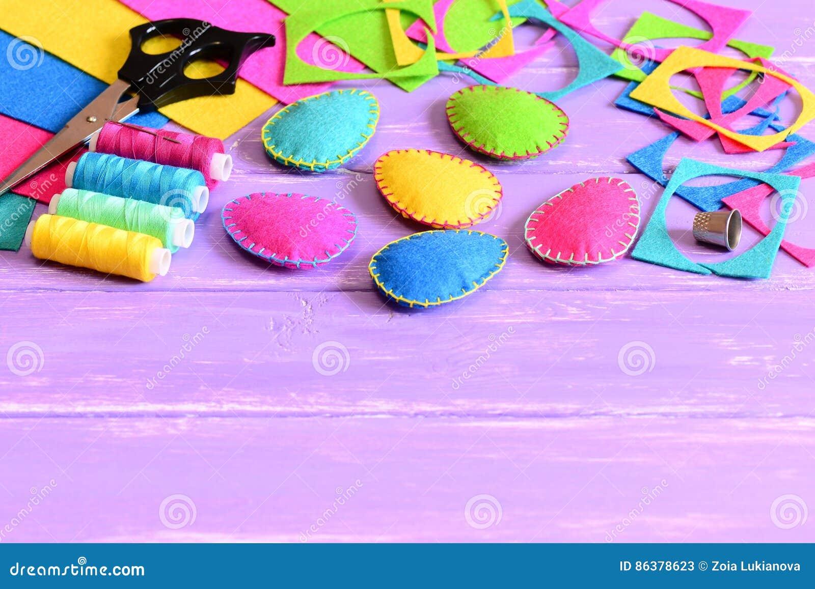 De kleurrijke gevoelde paaseierendecoratie, voelden bladen en schroot, schaar, draad, vingerhoedje op een lijst De gemakkelijke n