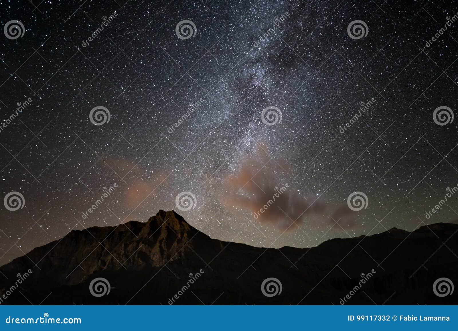 De kleurrijke gloeiende Melkwegboog en de sterrige hemel van hoogte omhoog op de Alpen