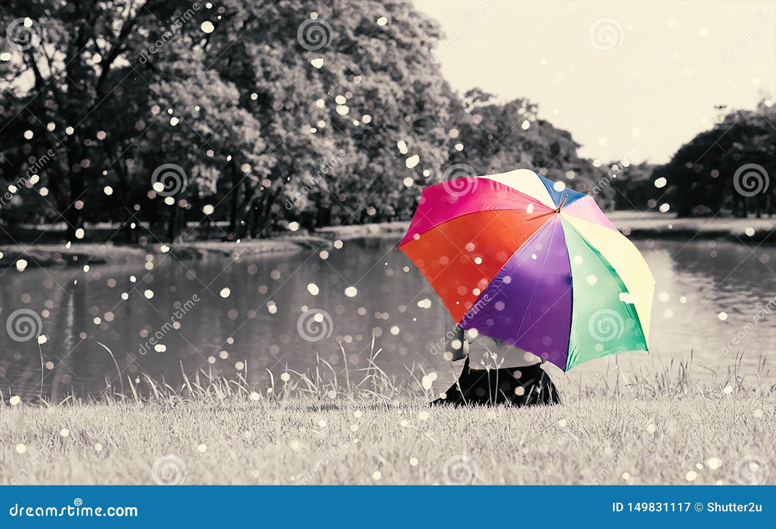 De kleurrijke greep van de regenboogparaplu door vrouw op grasgebied dichtbij rivier bij openlucht met hoogtepunt van aard en reg