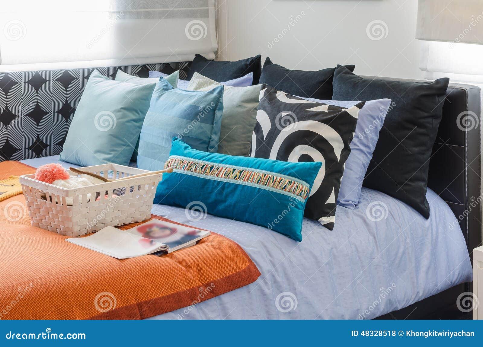 De Kleurrijke Hoofdkussens Met Mand Van Haken Op Bed Stock Foto