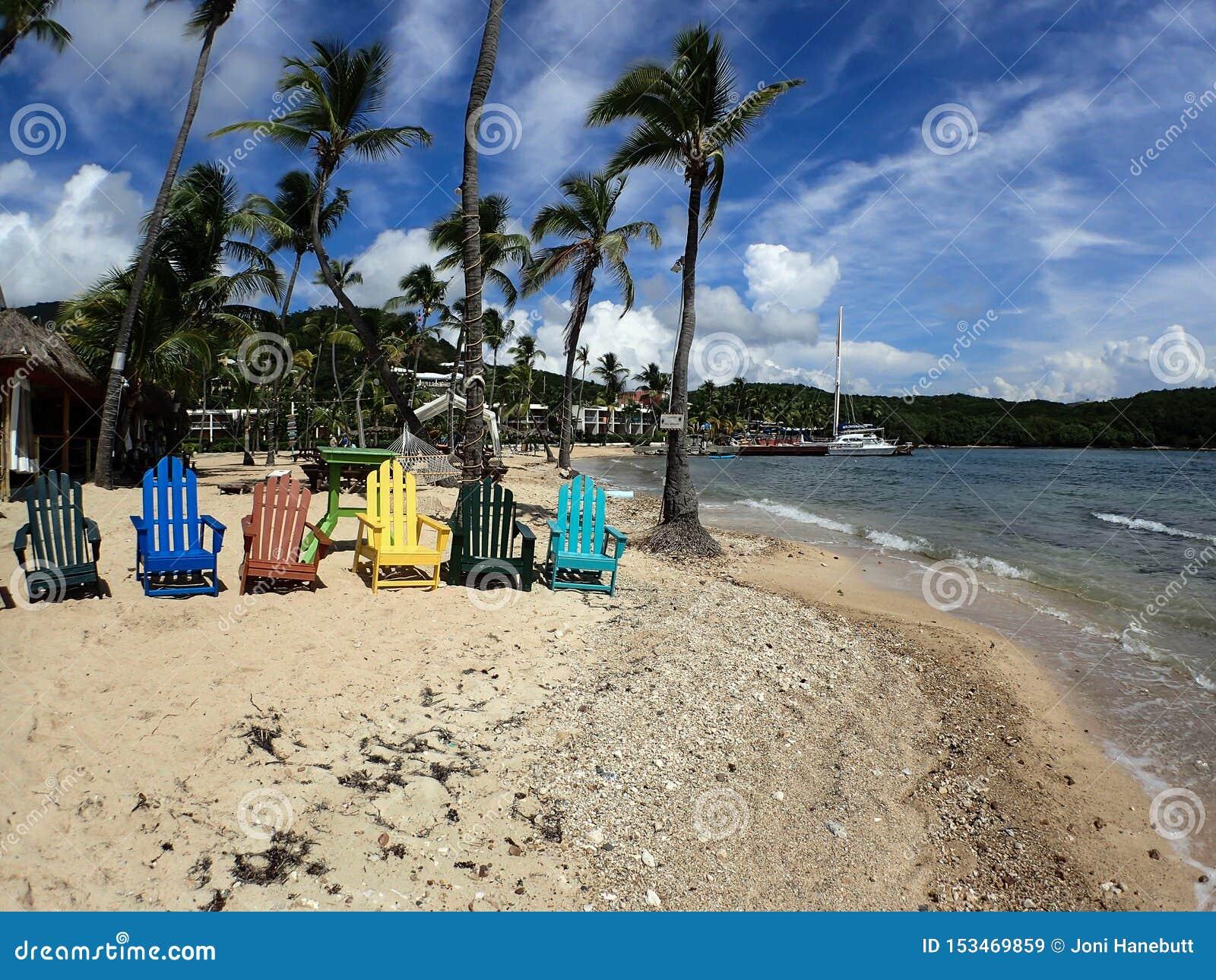 De kleurrijke ligstoelen, palmen, zeilboten bonden tot het dok, en mooi zandstrand