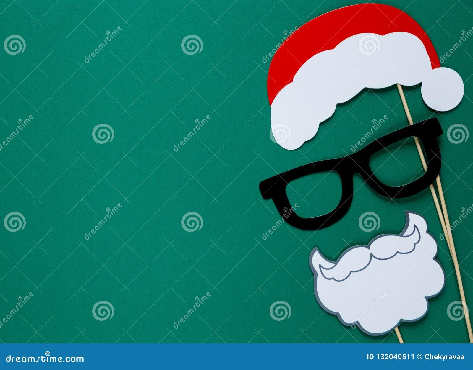 De kleurrijke steunen van de fotocabine voor Kerstmispartij - santahoed, glazen, baard op groene achtergrond