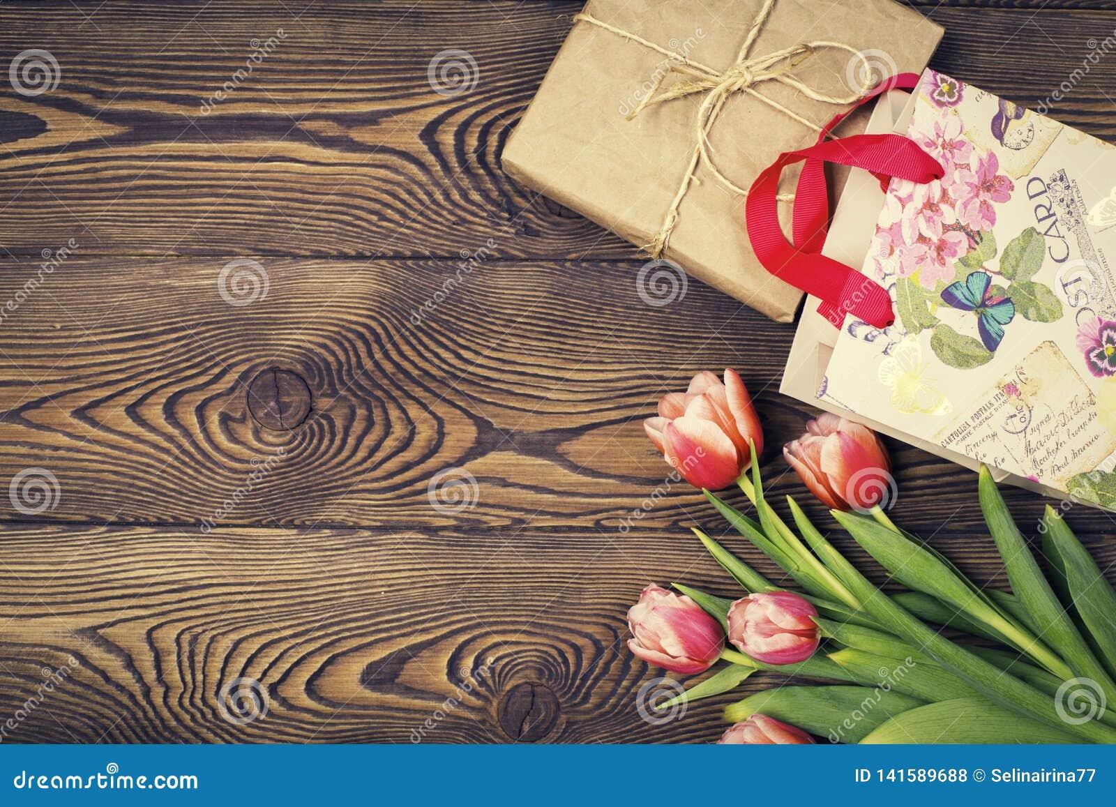 De kleurrijke tulpen en de gift in ambachtdocument en de gift doen op een houten lijst in zakken Hoogste mening met exemplaarruim