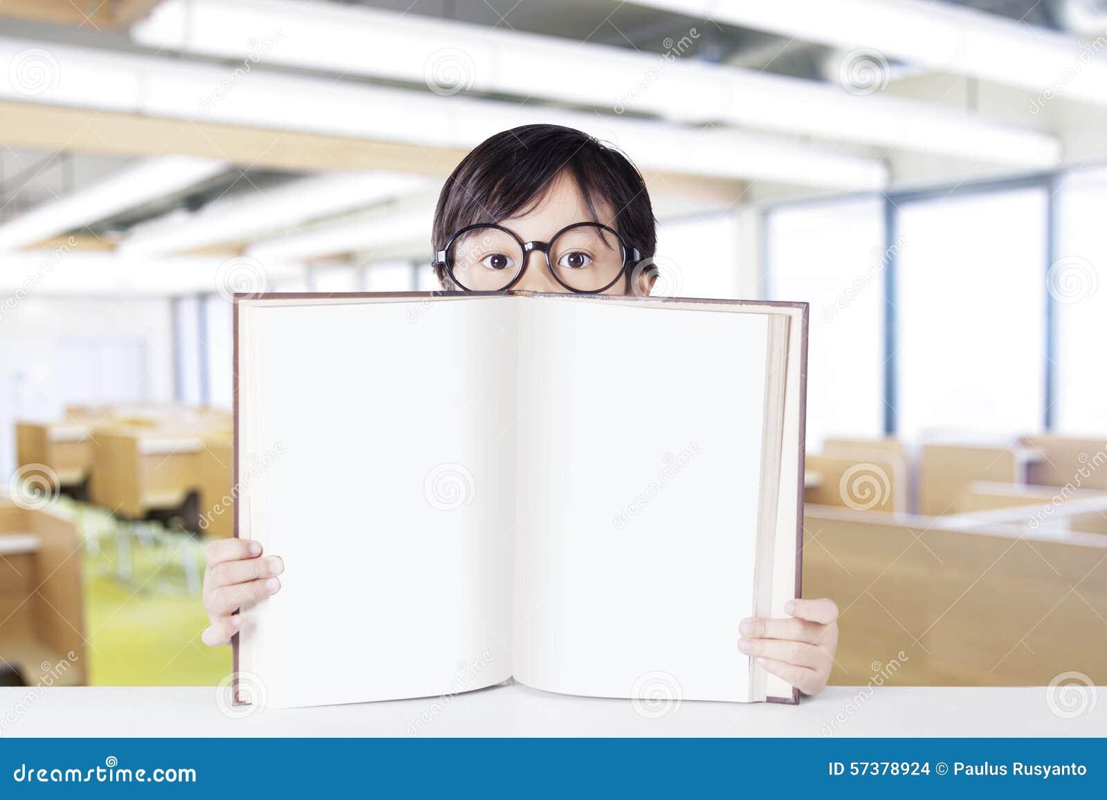 De kleuterschoolstudent toont leeg boek in klasse
