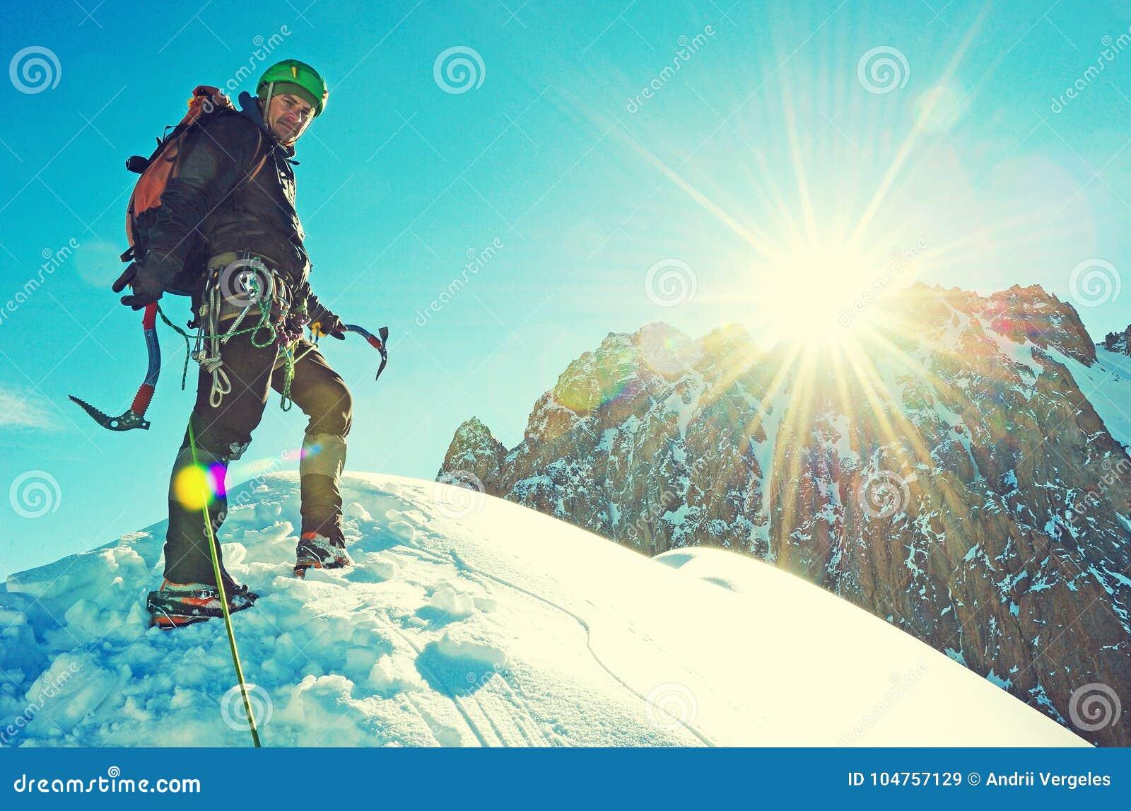 De klimmer bereikt de top van bergpiek Succes, vrijheid en geluk, voltooiing in bergen Het beklimmen van sportconcept