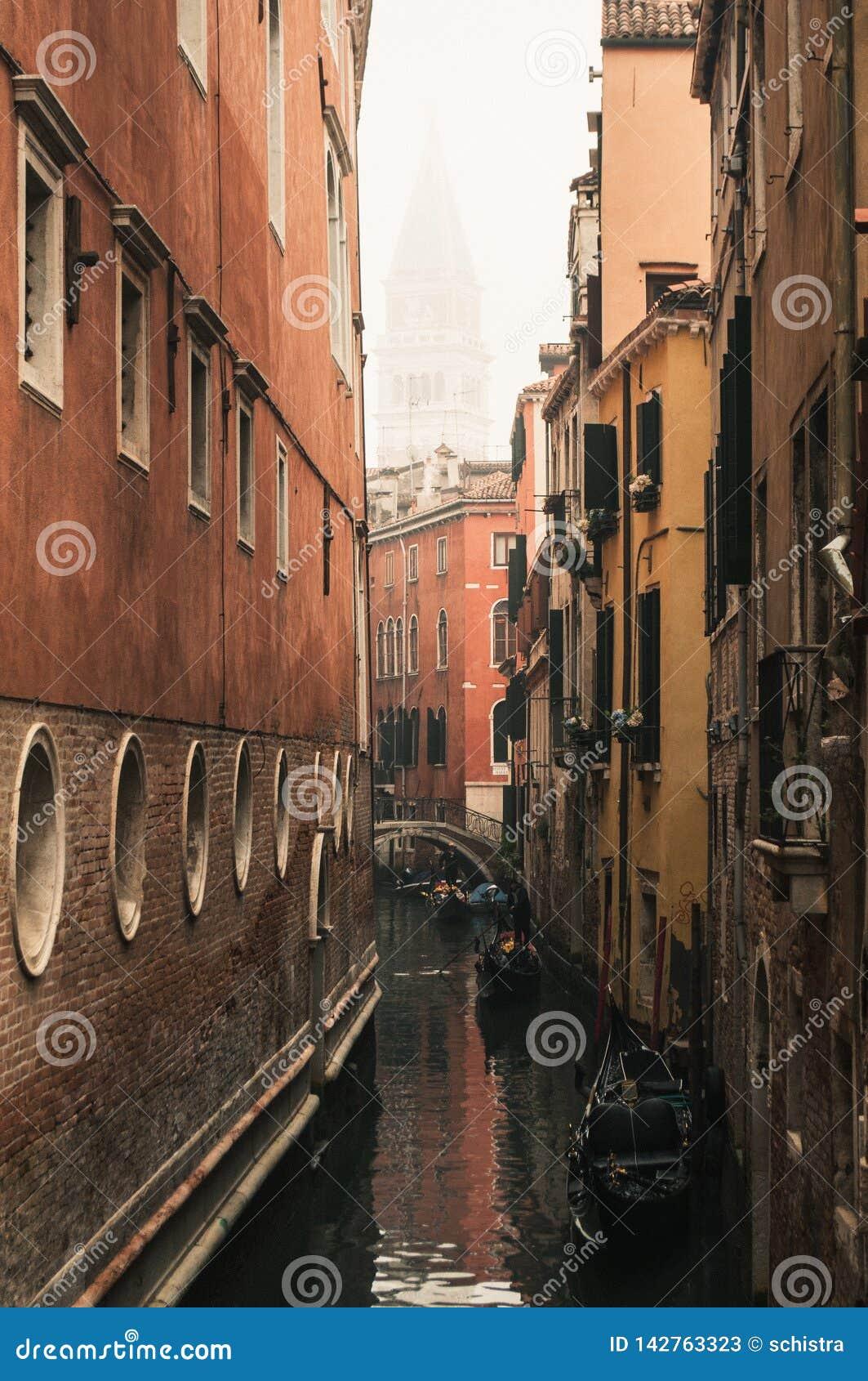 De klokketoren van San Marco van een steeg in Venetië op een mistige dag wordt gezien die