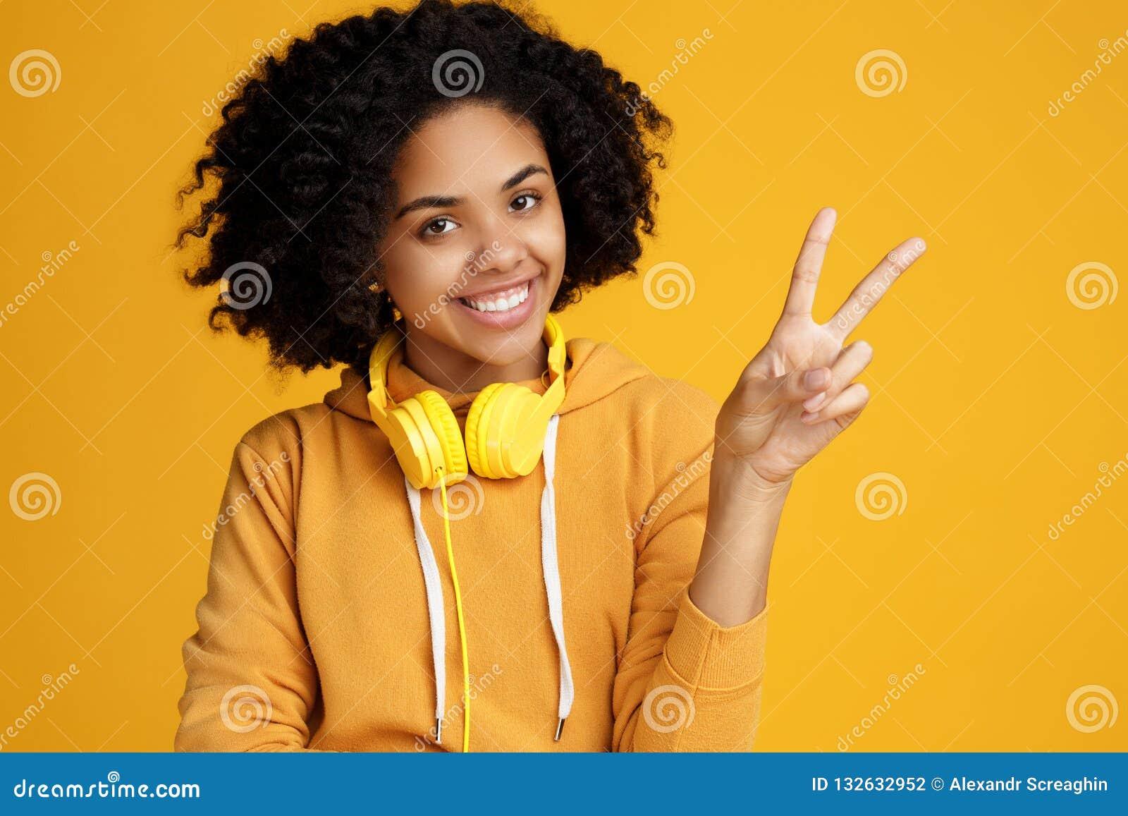 De knappe Afrikaanse Amerikaanse jonge vrouw met heldere glimlach kleedde zich in vrijetijdskleding en hoofdtelefoons die vredesg