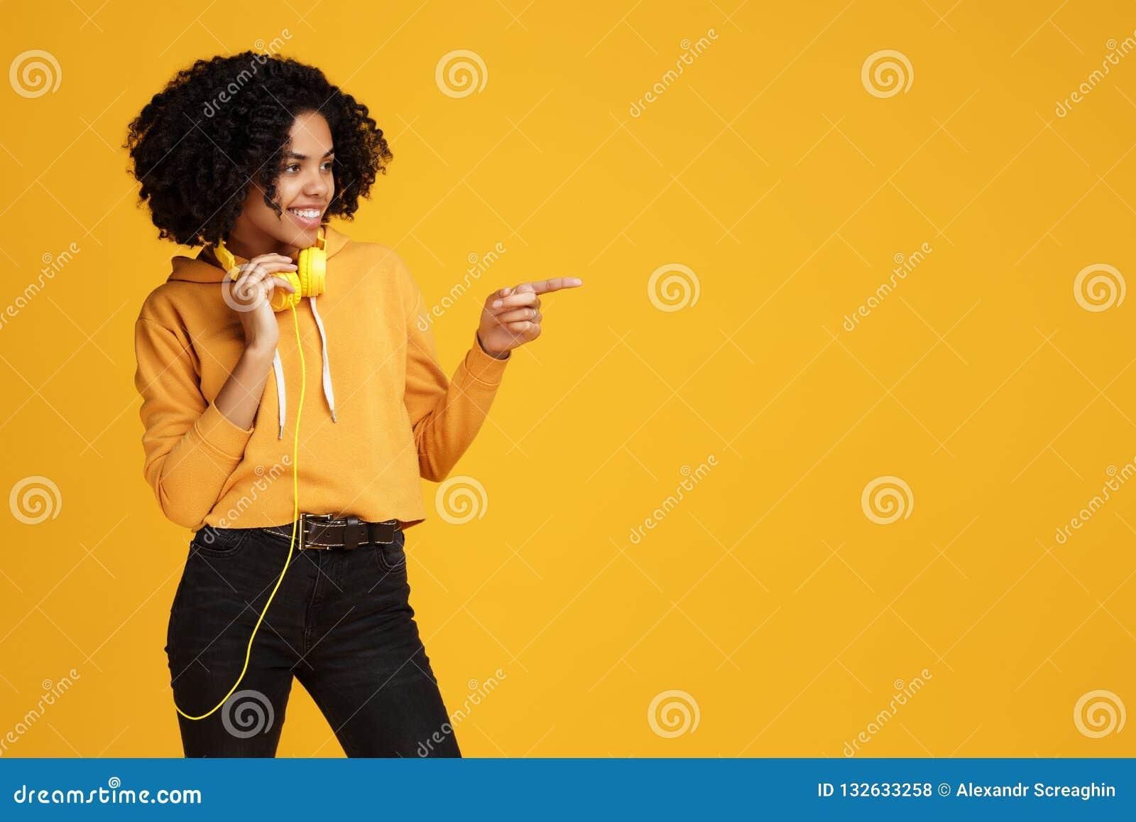 De knappe Afrikaanse Amerikaanse jonge vrouw met heldere glimlach kleedde zich in vrijetijdskleding en hoofdtelefoons die het ric