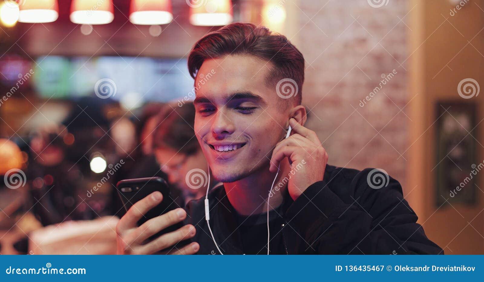De knappe jonge mens gebruikt hoofdtelefoons en zijn smartphone voor videogesprek Hij zit bij de bar dichtbij de neontekens vroli