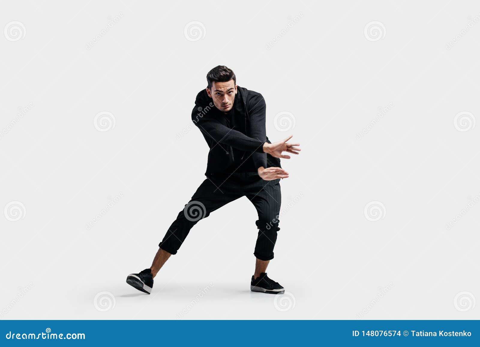 De knappe jonge mens gekleed in zwarte kleren is het dansen straatdans Hij maakt gestileerde bewegingen met zijn handen