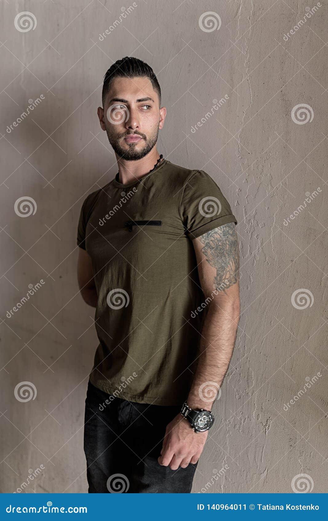 De knappe jonge mens met een modieus kapsel kleedde zich in vrijetijdskledingstribunes op de muurachtergrond