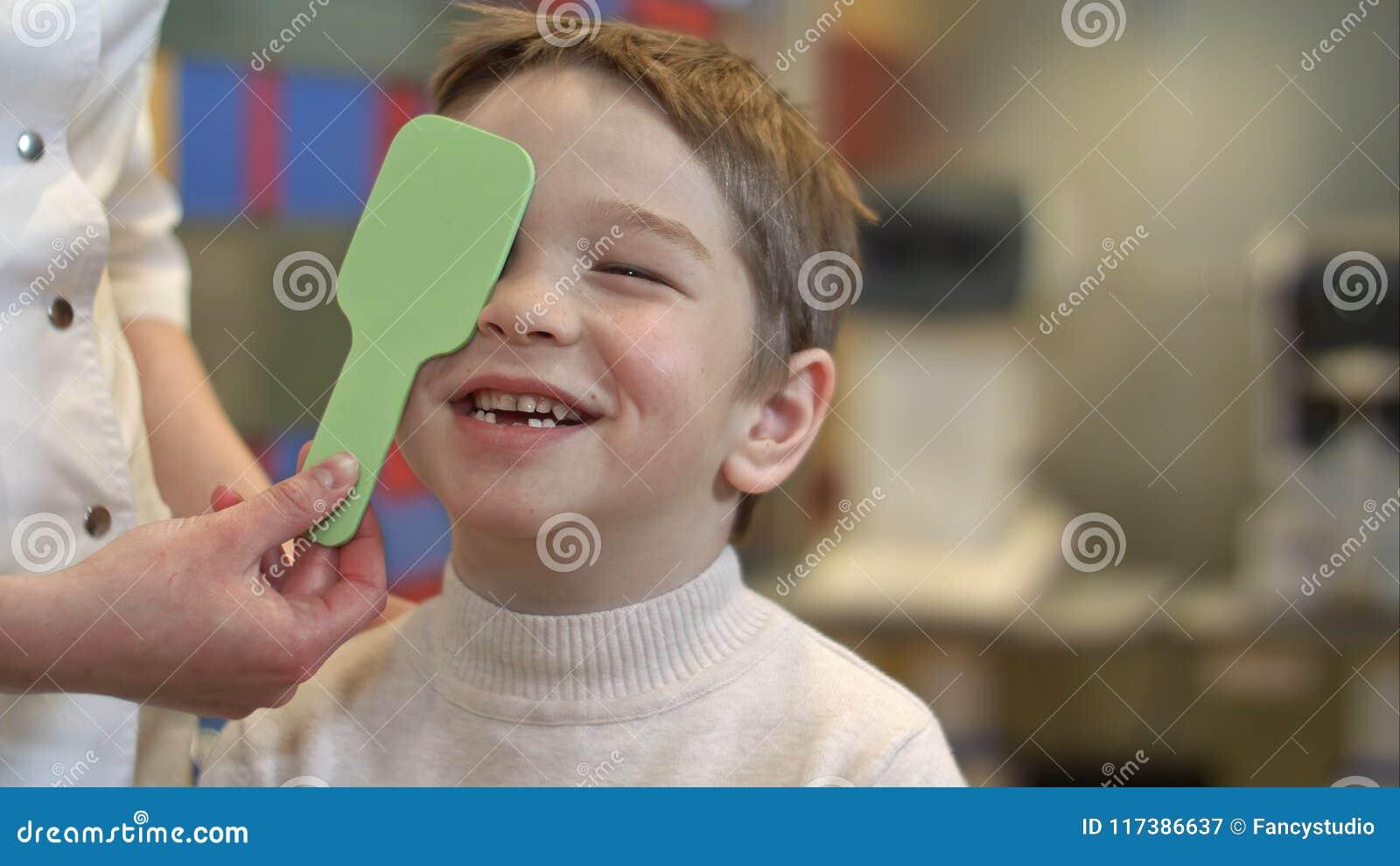 De knappe jongen onder oftalmoloogonderzoek sluit één oog probeert om brieven te lezen