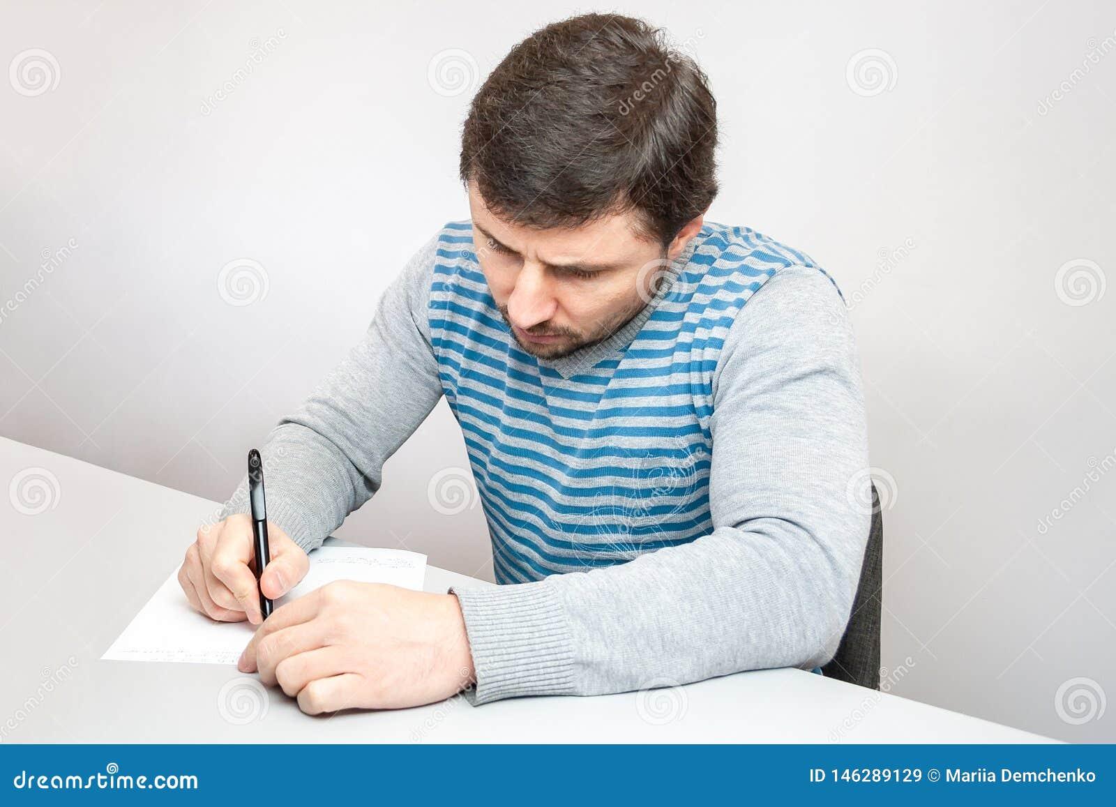 De knappe nadenkende mens in een gestreepte sweater zit bij de lijst en schrijft met een pen op papier