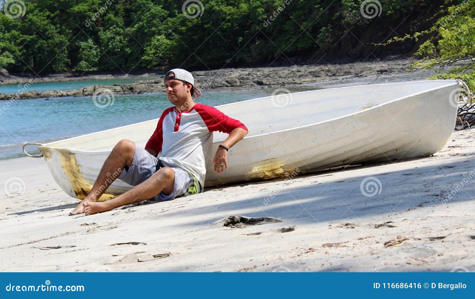 De knappe zitting van de schipbreukelingmens in het strand door een gesloopte boot die op hulp met oceaan en wildernis op de acht