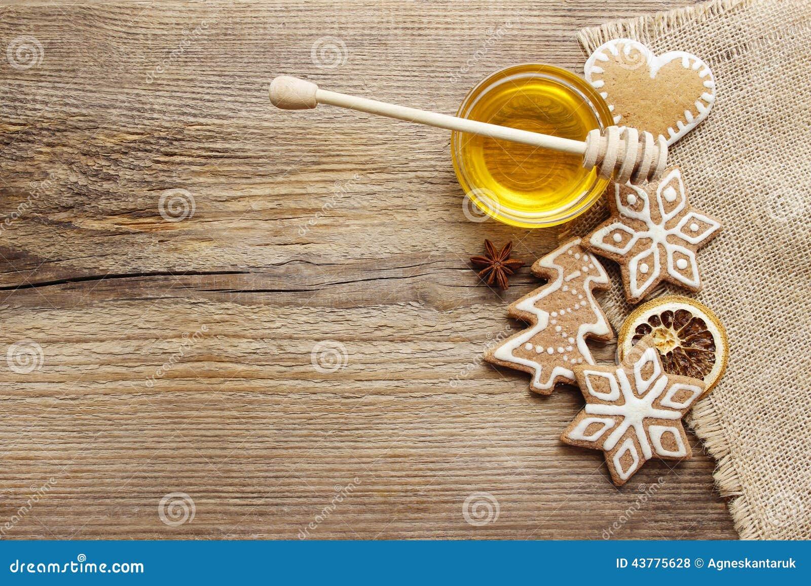 De koekjes van peperkoekkerstmis en kom honing op houten lijst
