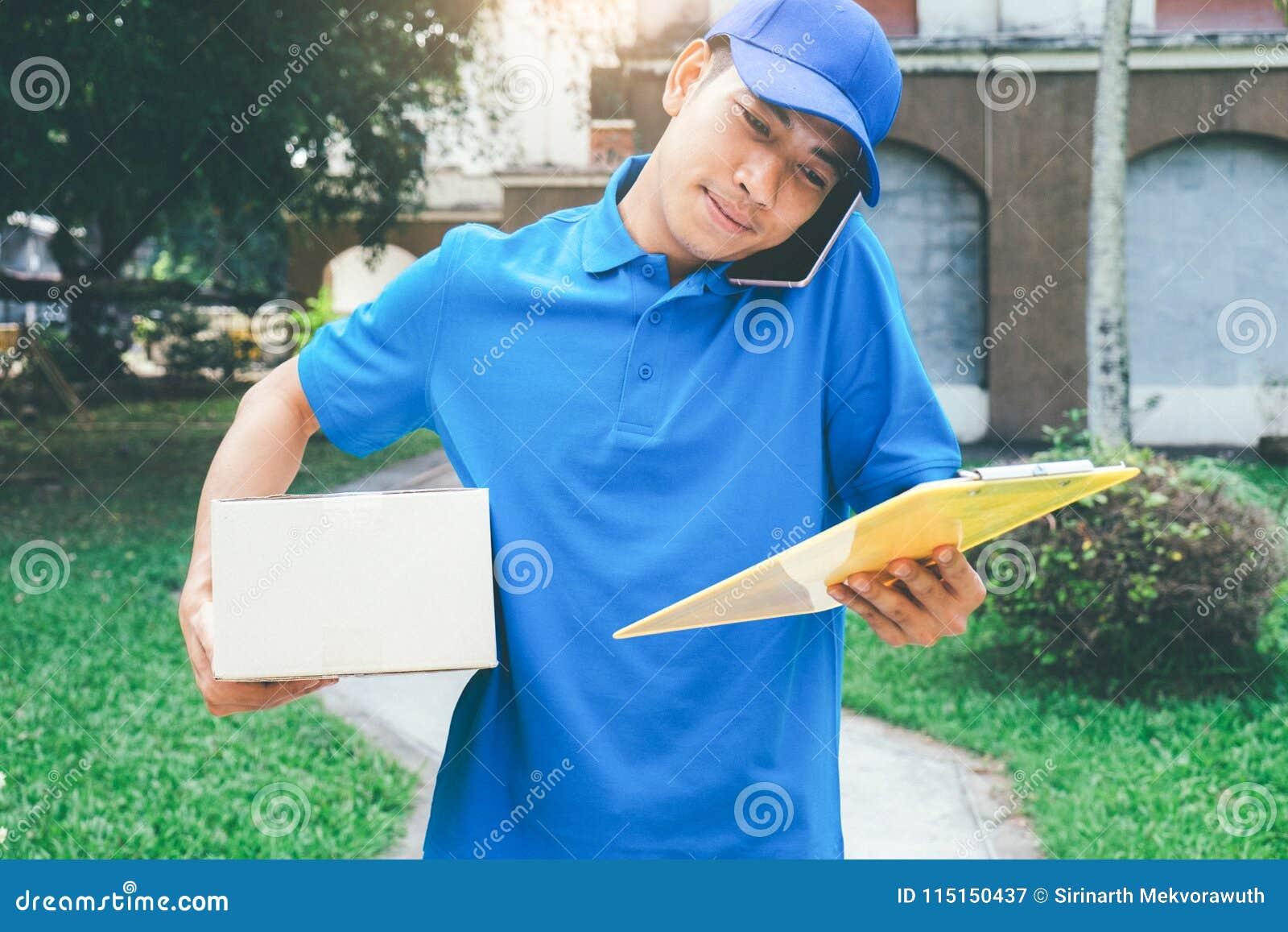 De koerier die van de leveringsdienst zich voor het huis met doos bevinden