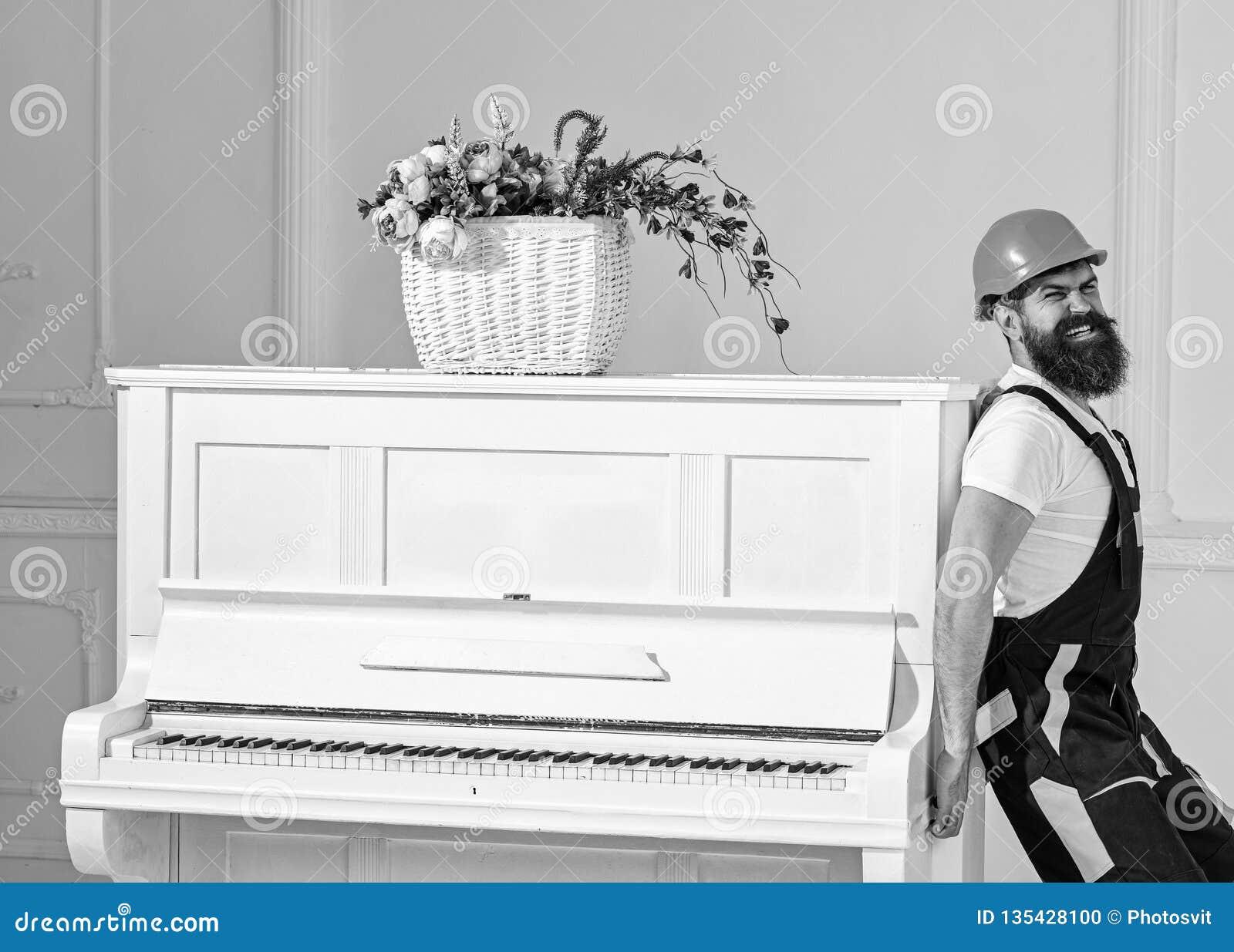 De koerier levert meubilair, beweging uit, verhuizing De mens met baardarbeider in helm en overallduwen, zette inspanningen aan