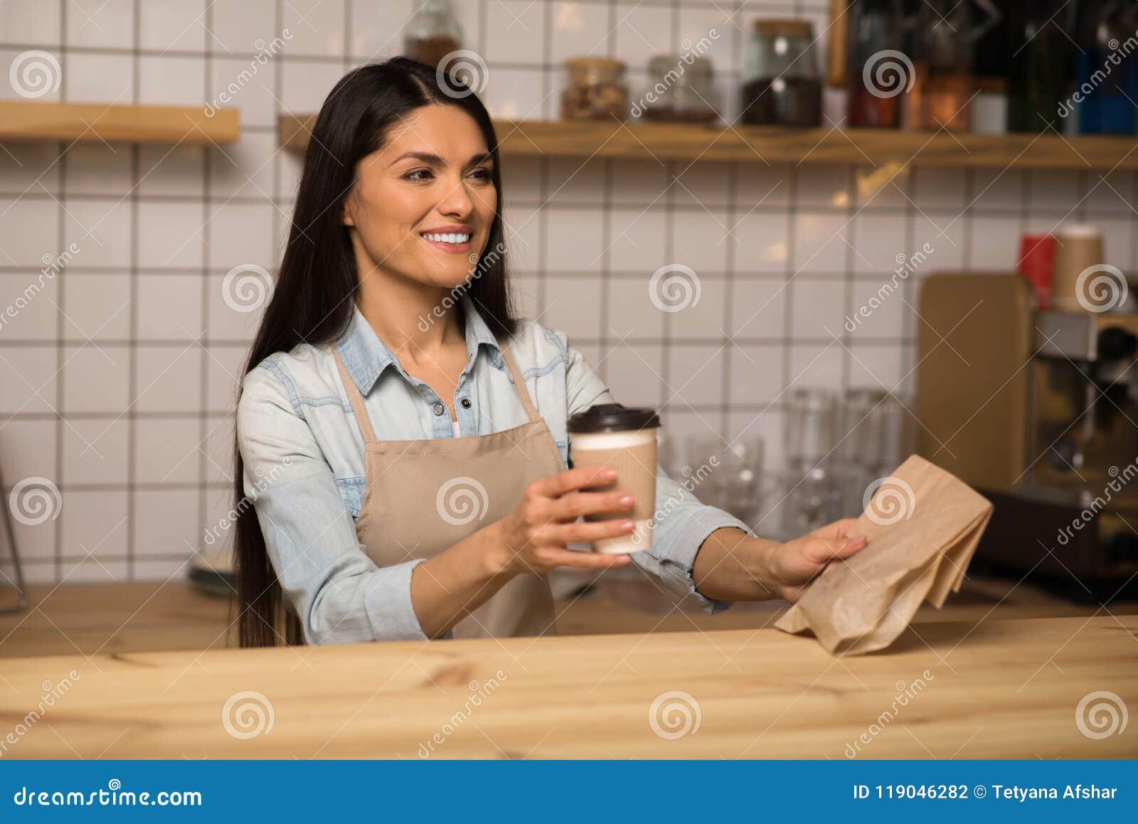 De koffie van de serveersterholding om te gaan en voedsel in koffie weg te halen