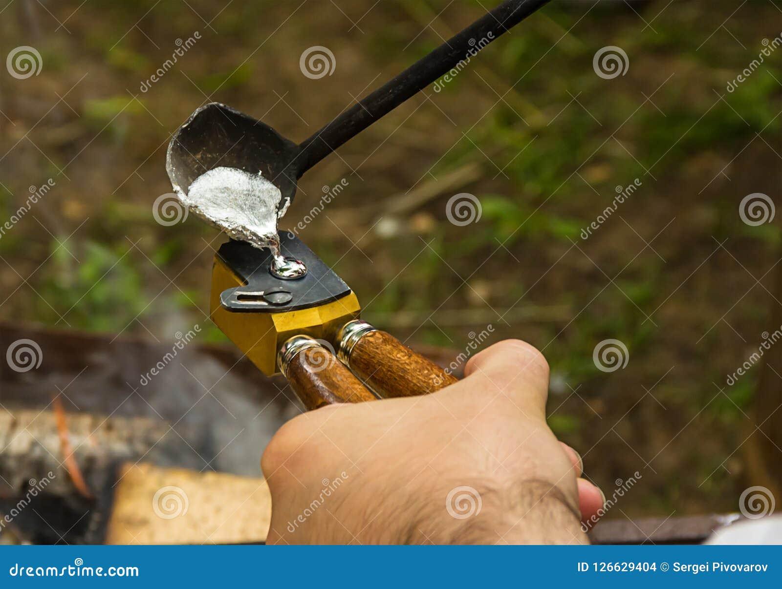 De kogel die om projectiel voor historische wapensmusketten maken het vloeibare metaal wordt gegoten is gevormde in hand vorm teg