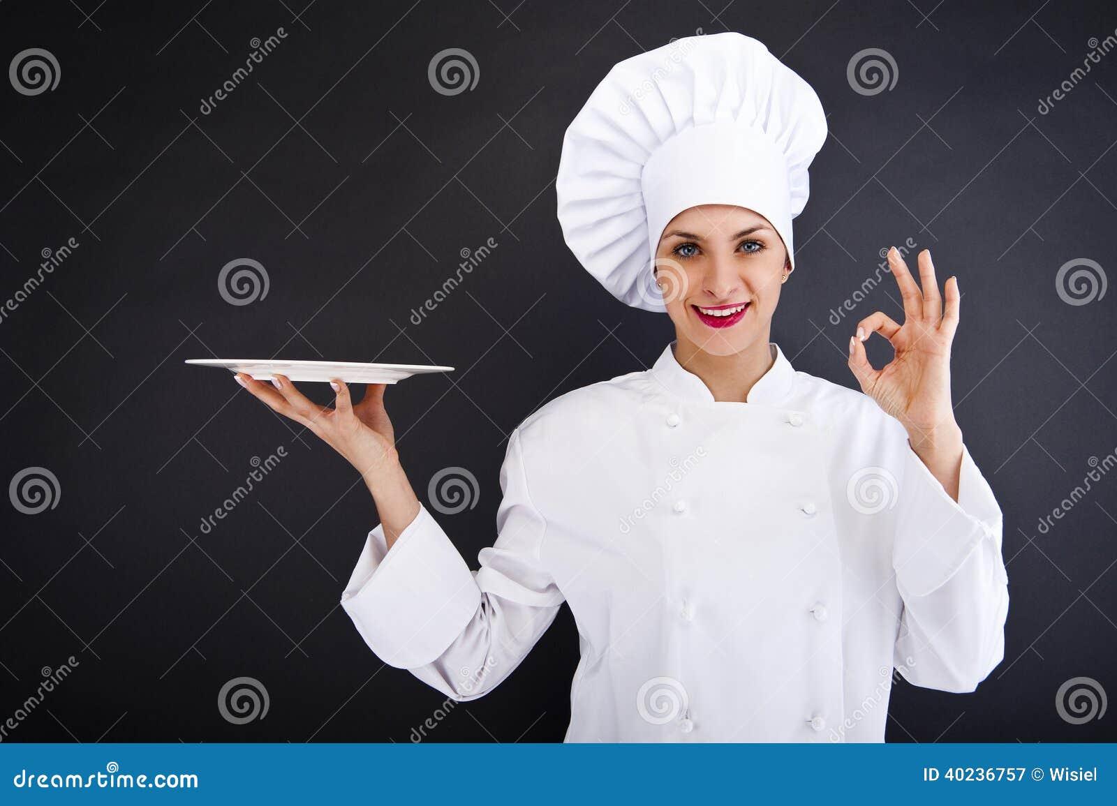 De kok of de chef-kok van de vrouw lege plaat dienen en gelukkig glimlachen die