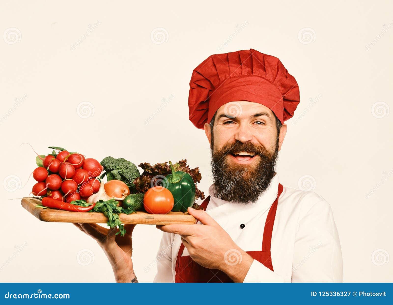 De kok met vrolijk gezicht in eenvormig Bourgondië houdt saladeingrediënten De chef-kok houdt raad met verse groenten het koken e