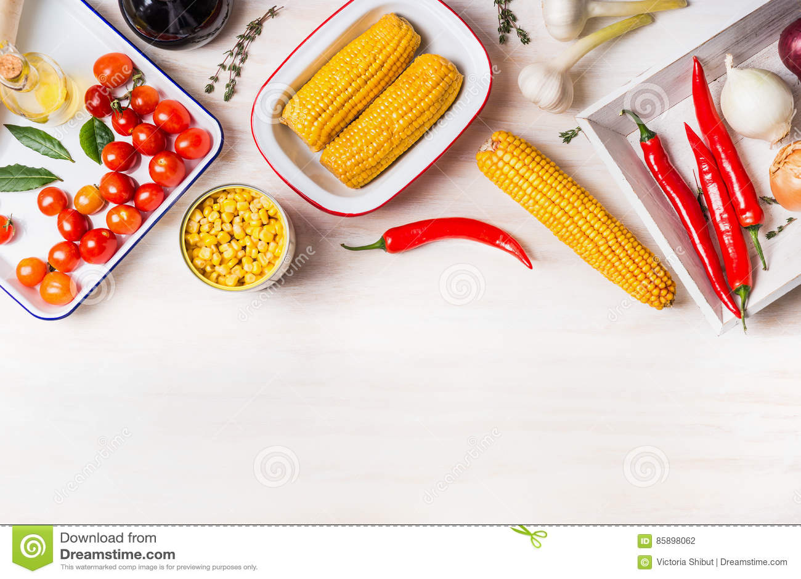 De kokende voorbereiding met korenaar, het ingeblikte en gekookte graan en de ingrediënten voor vegetarische schotel op witte hou