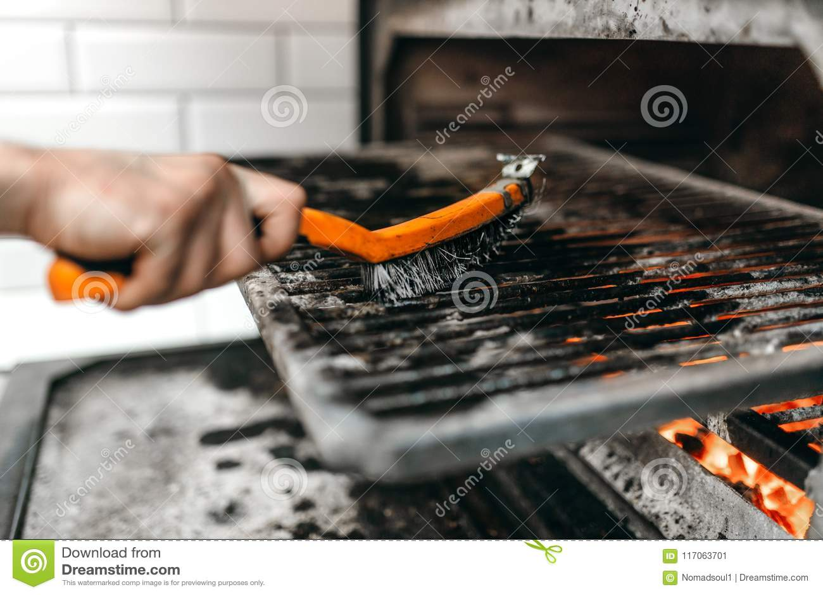 De kokhanden met metaal borstelen schoon de grilloven