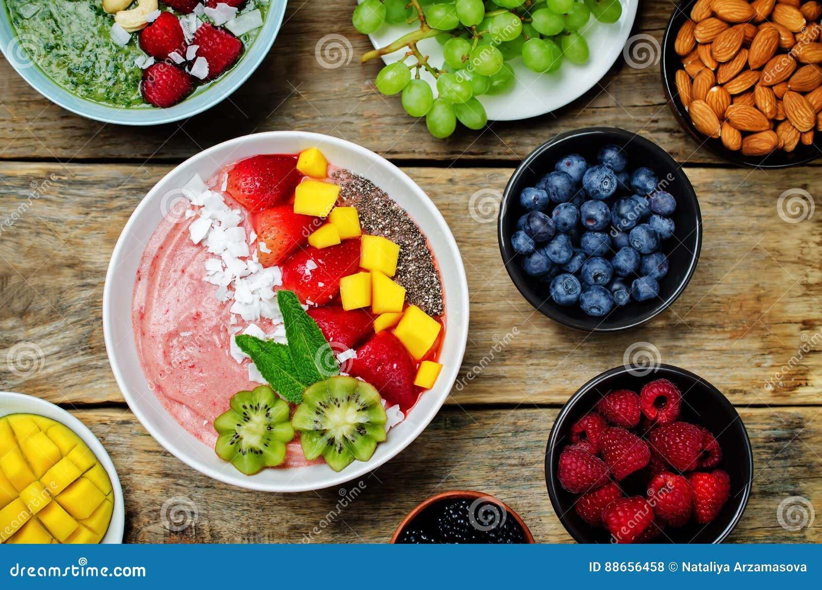 De kom van het aardbei smoothies ontbijt met kokosnotenvlokken, mango,